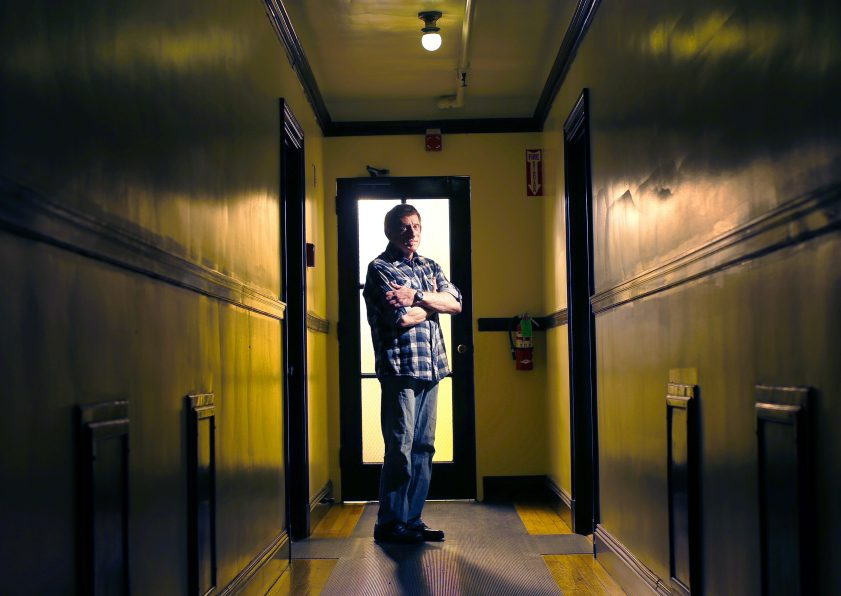 Jenson Steel, a longtime HIV patient at the India Street clinic who helped others transition to a new health care provider, stands in the corridor outside his West End apartment. The directed transfer of patients to a new facility caused