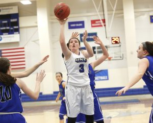Sadie Nelson of UNE finds plenty of room to put up a shot in the second half near a few St. Joe's defenders. Nelson had 12 points in UNE's home win Monday night.