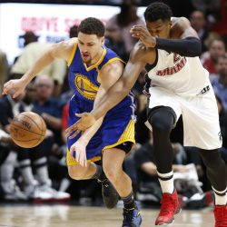 Golden State Warriors guard Klay Thompson, left, and Miami Heat center Hassan Whiteside battle for a loose ball during the first half of a 105-102 win by the Heat Monday night at Miami.