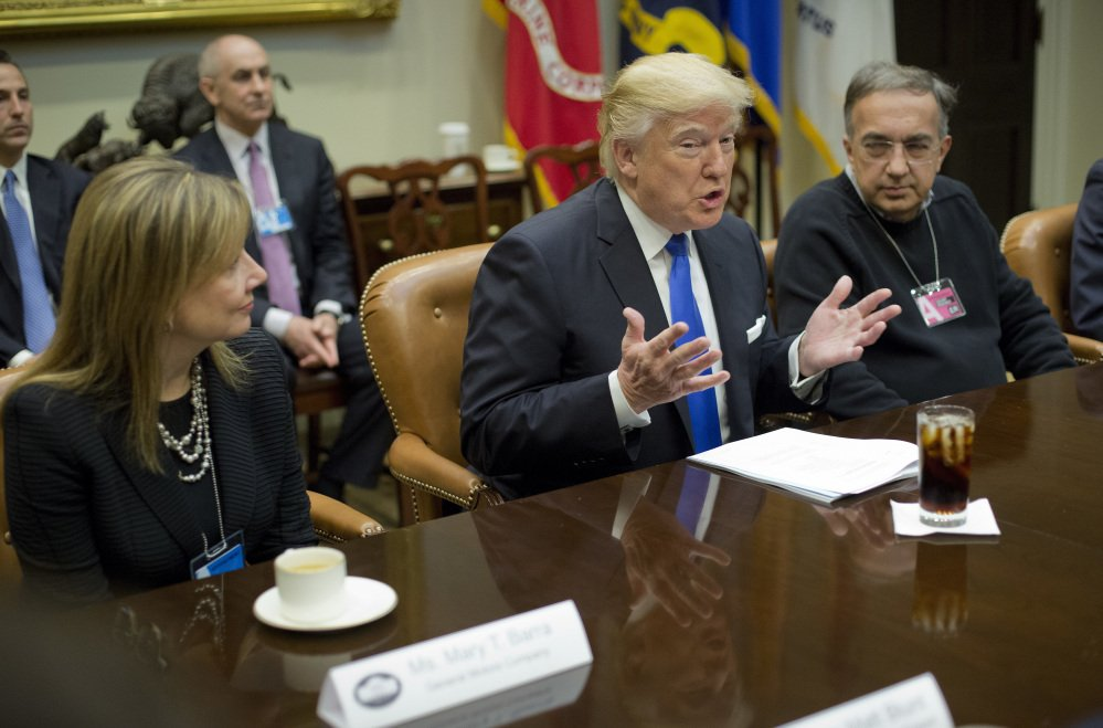 "GM chief executive Mary Barra, left, and Fiat Chrysler Automobiles CEO Sergio Marchionne, right, listen Tuesday to President Trump at the start of a meeting with automobile leaders at the White House. Trump said his administration will keep ""real regulations that mean something"" but curtail those he believes hamper business."
