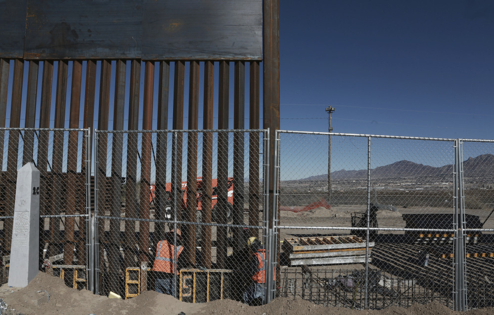 Workers continue work raising a taller fence in the Mexico-U.S. border area separating the towns of Anapra, Mexico, and Sunland Park, New Mexico, on Wednesday. U.S. President Trump signed a directive Wednesday to begin construction on a new border wall.