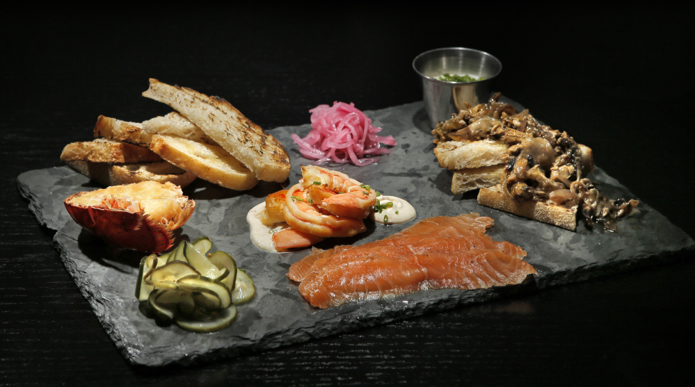 A smoked & cured board, including mussels escabeche, spicy shrimp, smoked lobster tail and salmon at Row 34.