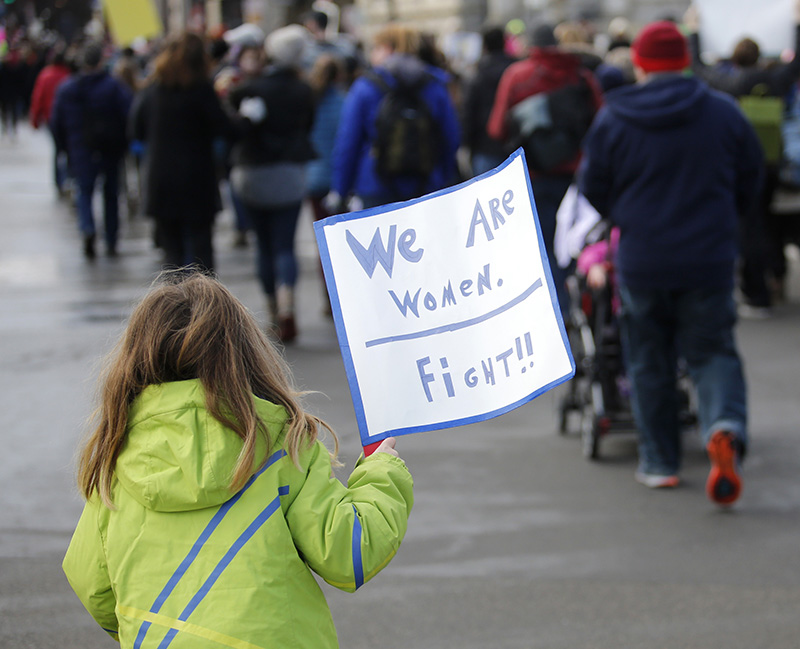 Cecilia Hopkins, 6, of Eastport holds a sign while marching with thousands of others along Congress Street for the Women's Walk on Saturday, Jan. 21, 2017.