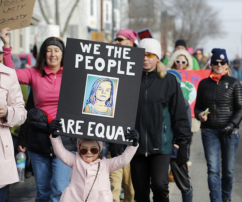 Lily Bienek, 3, of Falmouth holds a sign while marching with her mother on Saturday.