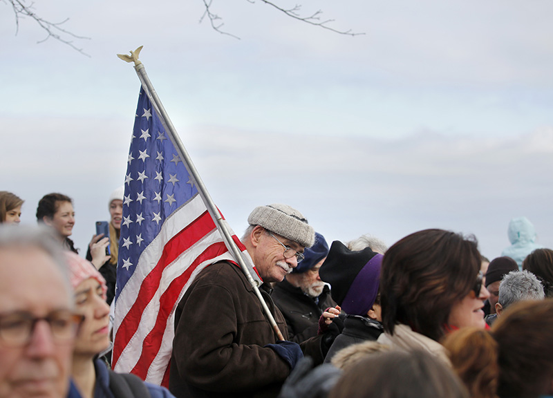 Phil  Cloutier of Portland carries a flag as he arrives at the Eastern Promenade before marching on Saturday.