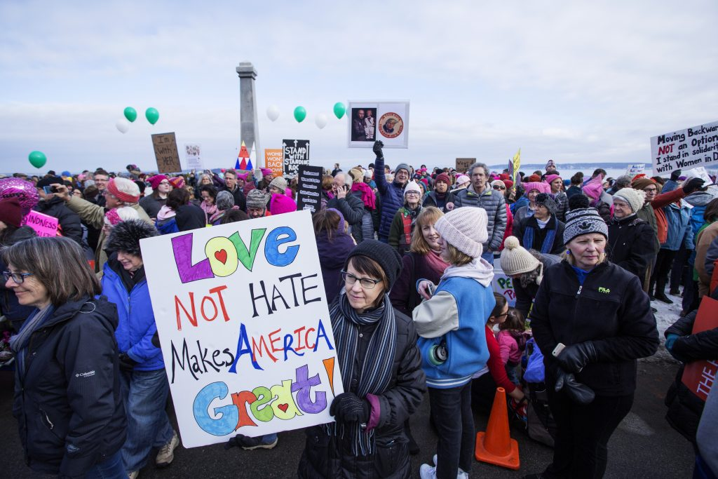 Diane Murphy, center, of Portland gathers with thousands of other marchers at the Eastern Promenade for the Women's Walk on Saturday.