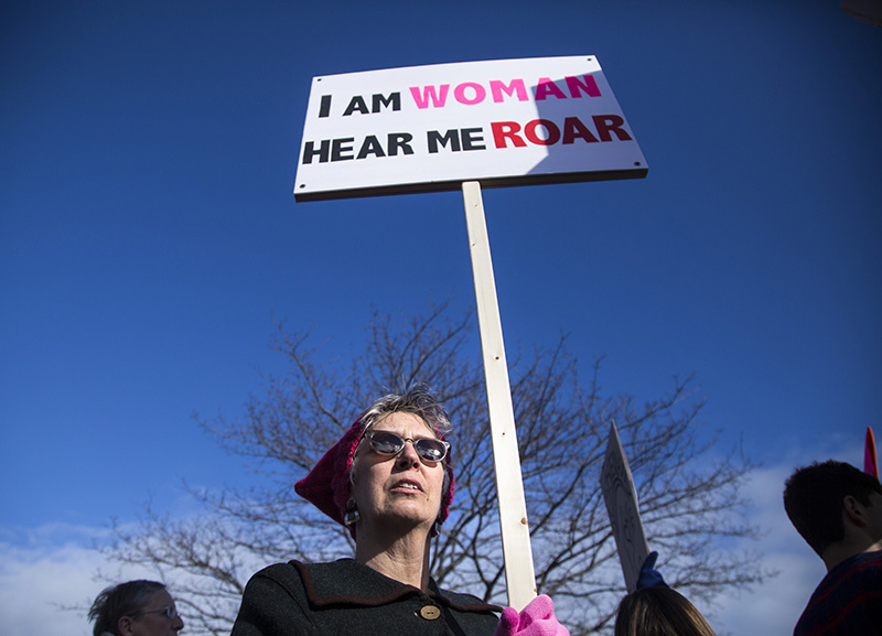 Margaret Russell of Byfield, MA carries a home-made sign while falling into line for the march.