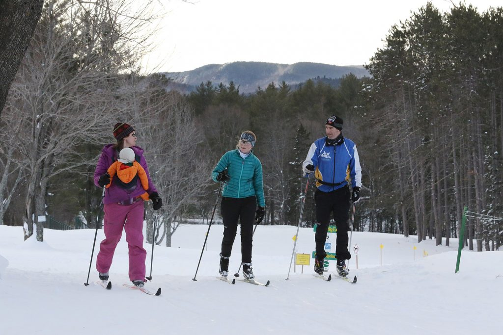 Beth Weisberger, left, carries Billie, 10 months, as she skis with Lilo Bean, center, and Brad Clarke. The Bethel Village Ski Center at the Bethel Inn Resort provides the rental space as well as the grooming equipment and fuel to sculpt 18 miles of trails.