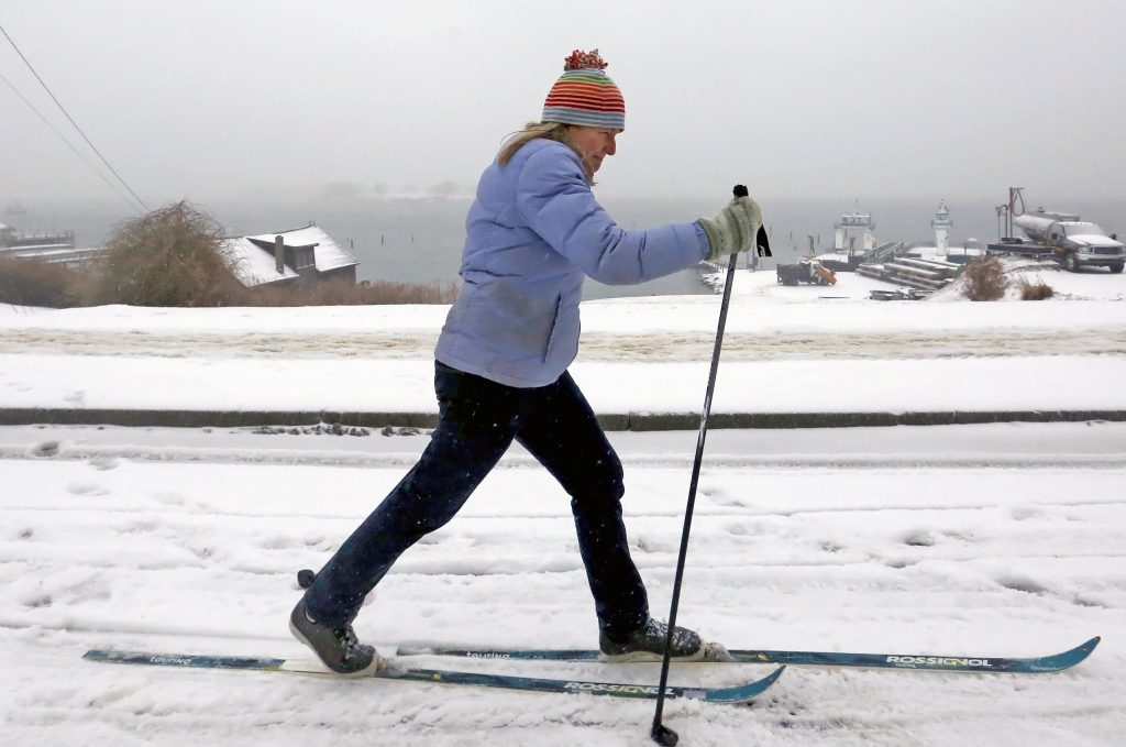 Leah Day skis along Island Avenue on Peaks Island during a winter storm on Tuesday.