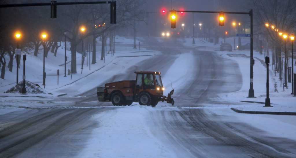 A snow plow works on the intersection of Spring and Center streets in Portland.