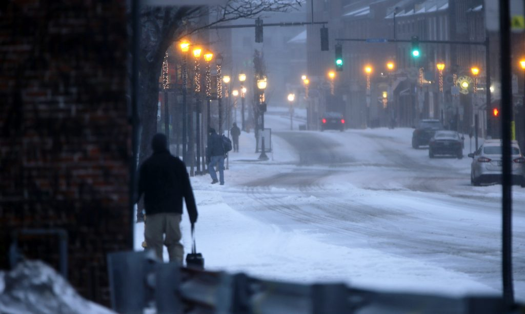 Pedestrians trudge through snow and ice pellets on Fore Street in Portland during a winter storm on Tuesday.