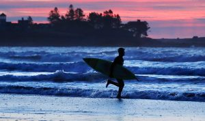 A surfer heads to the water before sunrise on a recent morning at Higgins Beach in Scarborough.