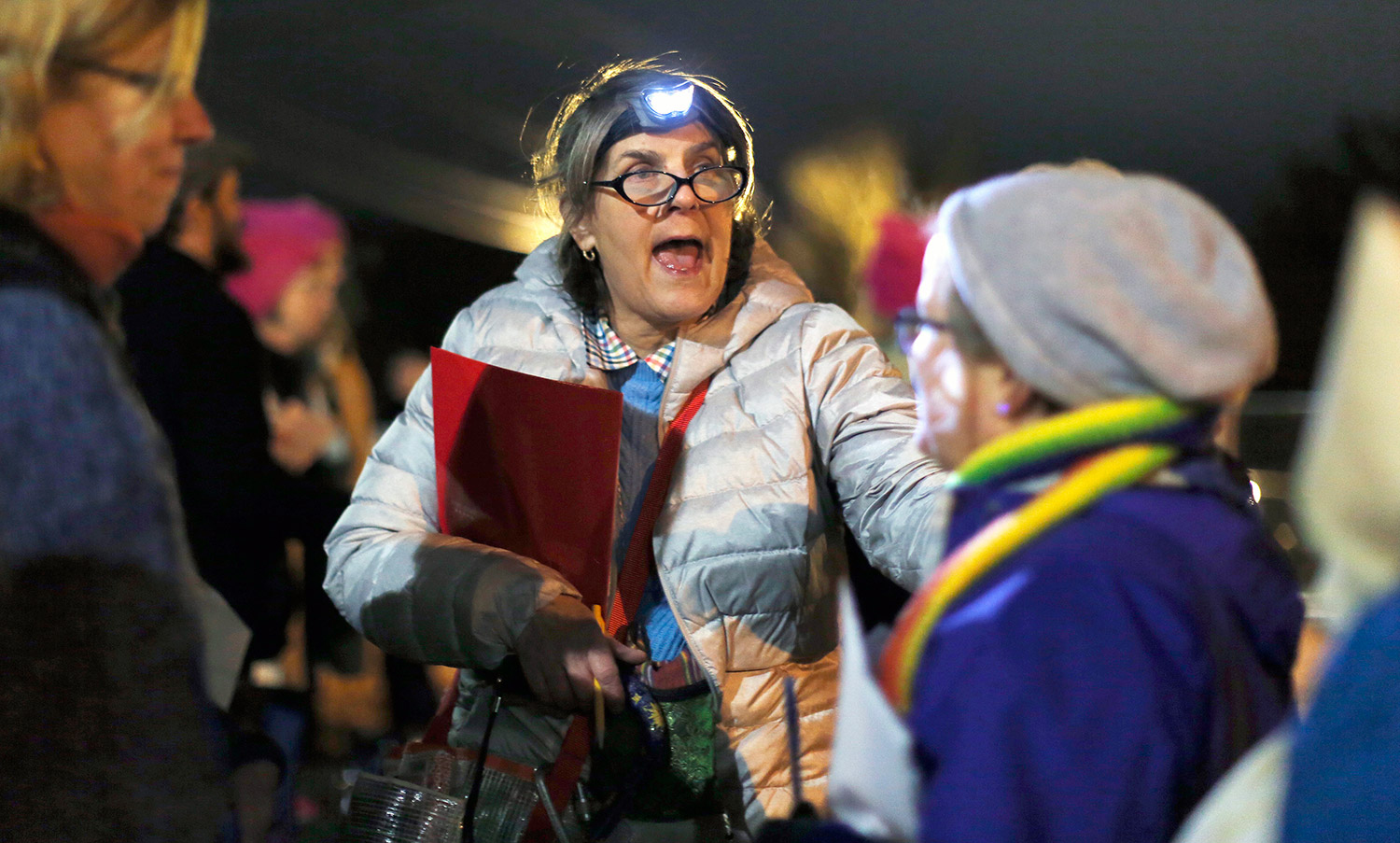 Group organizer Judy Gove talks to other protesters as they wait to board a bus Friday night for the Women's March on Washington.