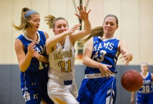 Falmouth forward Hadley Wiggins and Kennebunk forward Madison Lux, right, battle beneath the boards for a rebound during Monday's game. Kennebunk forward Alaina Schatzabel is at left.