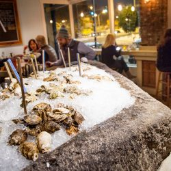 A selection of oysters chill in the ice-filled well of large block of granite at Eventide restaurant in Portland.