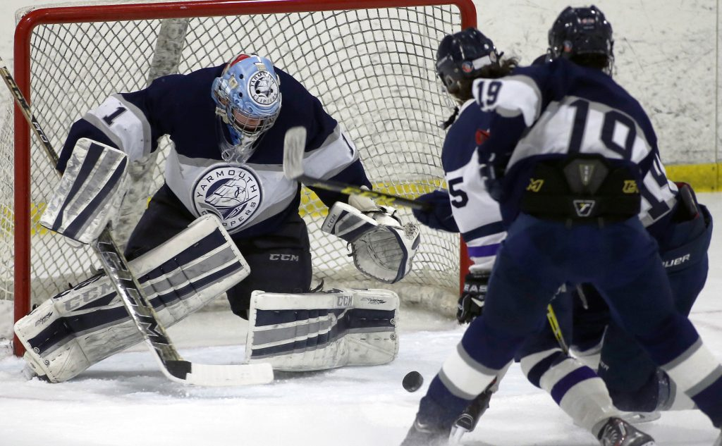 Yarmouth goalie Dan Latham drops down for a save against Portland/Deering.