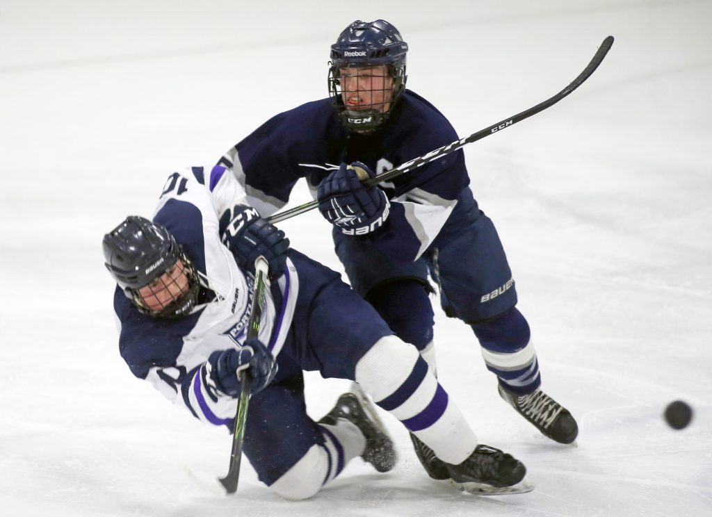 Yarmouth's Chris Romano uses his stick to knock down Portland/Deering's Alex McGonagle.