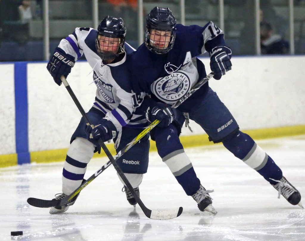 Portland/Deering's Sam Shaw and Yarmouth's Cooper May vie for the puck.