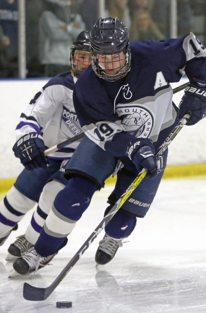 Yarmouth's Cooper May skates toward the goal while Portland/Deering's Sam Shaw pursues.