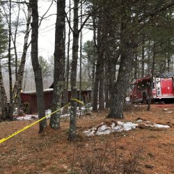 Fire crews and others work at a home on Cattle Pond Road in Washington a few hours after a fatal fire on Monday.