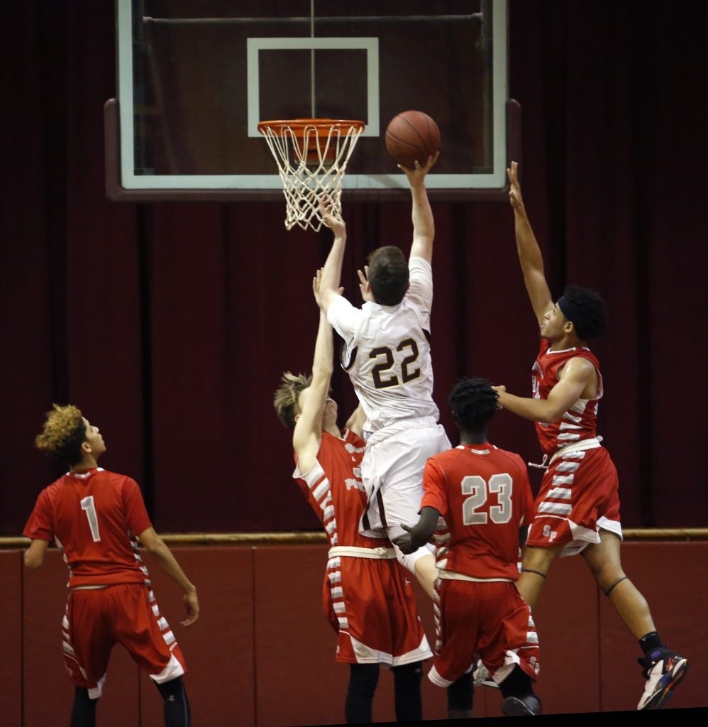David Keohan of Thornton Academy puts up a shot after drawing a crowd of South Portland defenders in the second half.
