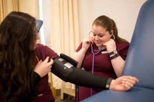 Rachel Souza, right, practices checking blood pressure on her fellow nursing student Hannah Pazmany during their adult care class Tuesday at St. Joseph's College. The college has received a $1.5 million grant from the Harold Alfond Foundation to support the creation of a new nursing center.