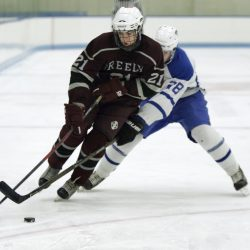 Jack Saffian of Greely carries the puck past Nathaniel Jewett of Kennebunk at the Harold Alfond Forum at the University of New England in Biddeford on Monday. Kennebunk won the game 5-1.