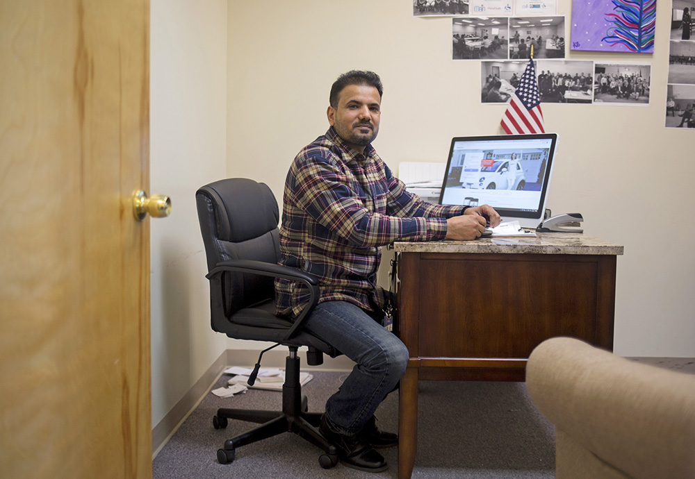 Faysal Kalayf, working in his office as vice president of the Iraqi Community Association of Maine, says immigrants are calling to ask how President Trump's actions will affect their legal status and loved ones.