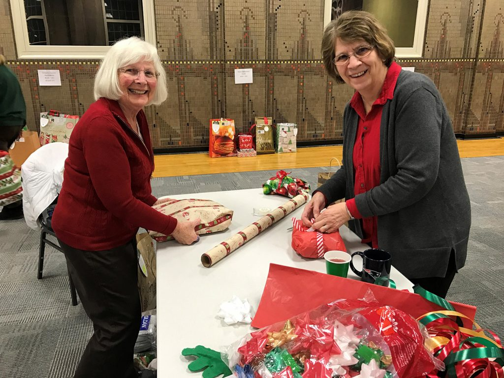Rita Smith and Nancy Bartlett wrap gifts for area seniors who otherwise might have gone without this holiday season. The event was held at the Home Instead office in Gorham.