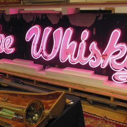 A marquee from the legendary Whisky a Go Go glows at the Saco River Auction Co. in Biddeford. The sign that adorned the West Hollywood club during the heyday of punk, new wave and grunge in the 1980s and '90s will go up for auction on Wednesday.