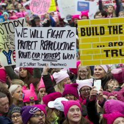 Women with bright pink hats and signs begin to gather early and are set to make their voices heard on the first full day of Donald Trump's Women with bright pink hats and signs begin to gather early for the Women's March on Washington.