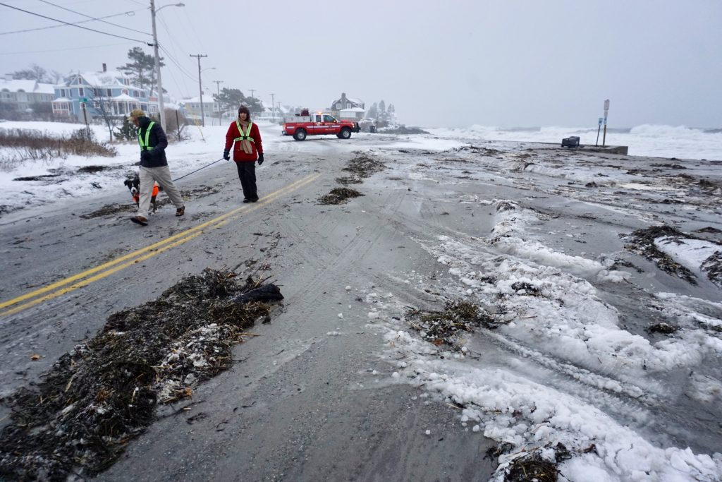 Ian Durham and his wife Alyson walk with their dog Lauren near Mother's Beach in Kennebunk, where the road is covered with debris from waves splashing over the sea wall, on Tuesday morning.