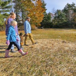 """Walter and Aaron Morse, with their children Paige and Joseph, walk through a field at their Patriot Ridge Homestead in Jefferson. The family will be featured Sunday on the first episode of a new a television show called """"Growing Home,"""" about veterans working in agriculture throughout Maine. Photo courtesy of Up Country Productions"""