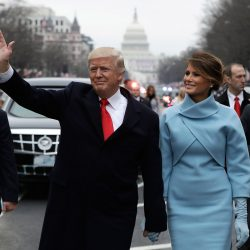 President Donald Trump waves as he walks with first lady Melania Trump during the inauguration parade on Pennsylvania Avenue in Washington on Friday.