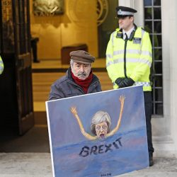 Artist Kaya Mar expresses his views with a painting of British Prime Minister Theresa May in front of the Supreme Court in London Tuesday.