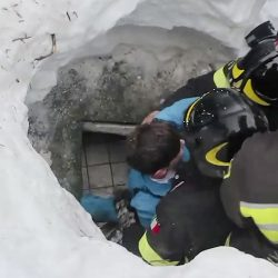 This frame from video shows Italian firefighters extracting a boy alive from under snow and debris.