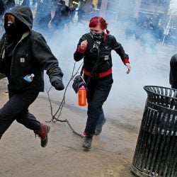 Activists run after being hit by a stun grenade while protesting against President Donald Trump on the sidelines of the inauguration in Washington Friday.