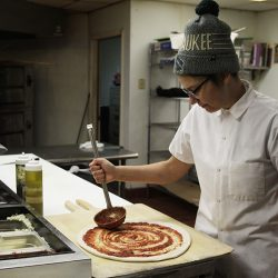 In this Jan. 9, 2017, photo, Andrea Ledesma spreads sauce on pizza dough at Classic Slice restaurant in Milwaukee. The 28-year-old has a four-year degree and quit a higher paying job because it made her miserable. Ledesma thought she would be making more at this point in her life and she's not alone. With a median household income of $40,581, millennials earn 20 percent less than boomers did at the same stage of life, despite being better educated, according to a new analysis of Federal Reserve data by the advocacy group Young Invincibles. (AP Photo/Carrie Antlfinger)