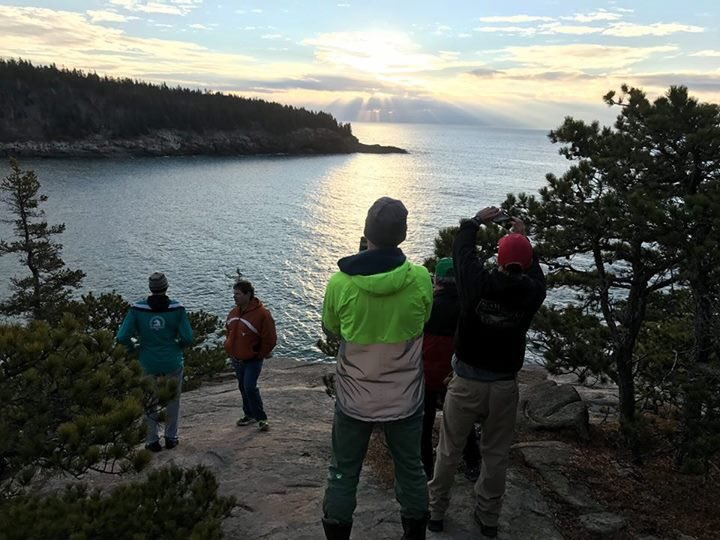 """Gary Allen's friends admire the """"RESIST"""" sign they wrote from the cliffs near Sand Beach in Acadia National Park on Sunday."""