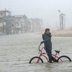 Jake Hart, 13, plays in the rising floodwater during a storm in Seal Beach, Calif., Sunday. The heavy downpour drenched Orange County in one of the heaviest storms of the year. Long Beach Airport received 3.87 inches, breaking the all-time daily record for rainfall.