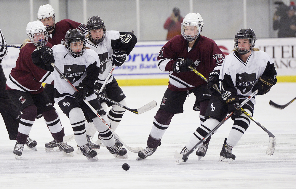 Greely and St. Dominic players battle for a loose puck during Thursday's game in Auburn, They are, from left, Molly Horton of Greely, Bugsy Hammerton and Kristina Cornelio of St. Dominic, Kylie Rogers of Greely and Avery Lutrzykowski of St. Dominic. The Saints won, 3-2.