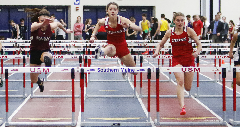 Ellen Shaw, center, of Scarborough clears the final hurdle on her way to victory in the senior 55-meter hurdles, helping the Red Storm win the girls' team championship.