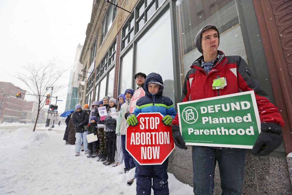About 30 anti-abortion protesters gathered outside Planned Parenthood's Congress Street office in Portland on Saturday to call for federal defunding of the reproductive health organization
