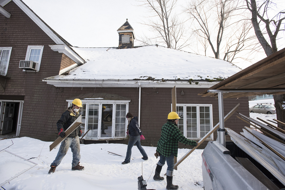 Workers employed by Barn Boards and More salvage wood molding and boards last week from 18 Dennis St. in Gardiner, the former estate of Frank E. Boston.
