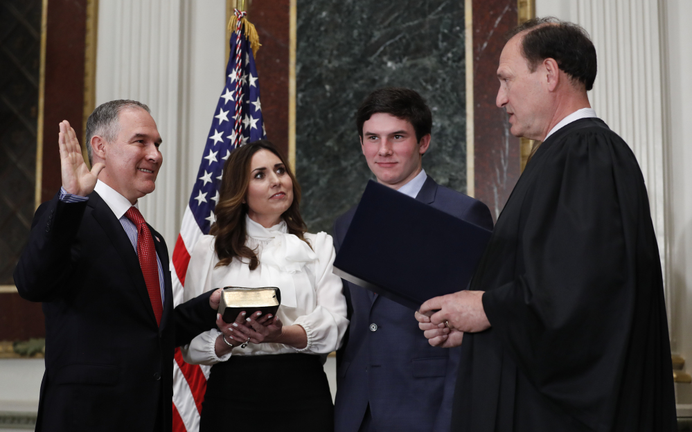 Supreme Court Associate Justice Samuel Alito swears in Scott Pruitt as the Environmental Protection Agency administrator in Washington on Friday. Holding the Bible is Marlyn Pruitt, wife of Scott Pruitt, as their son Cade Pruitt stands second from right.