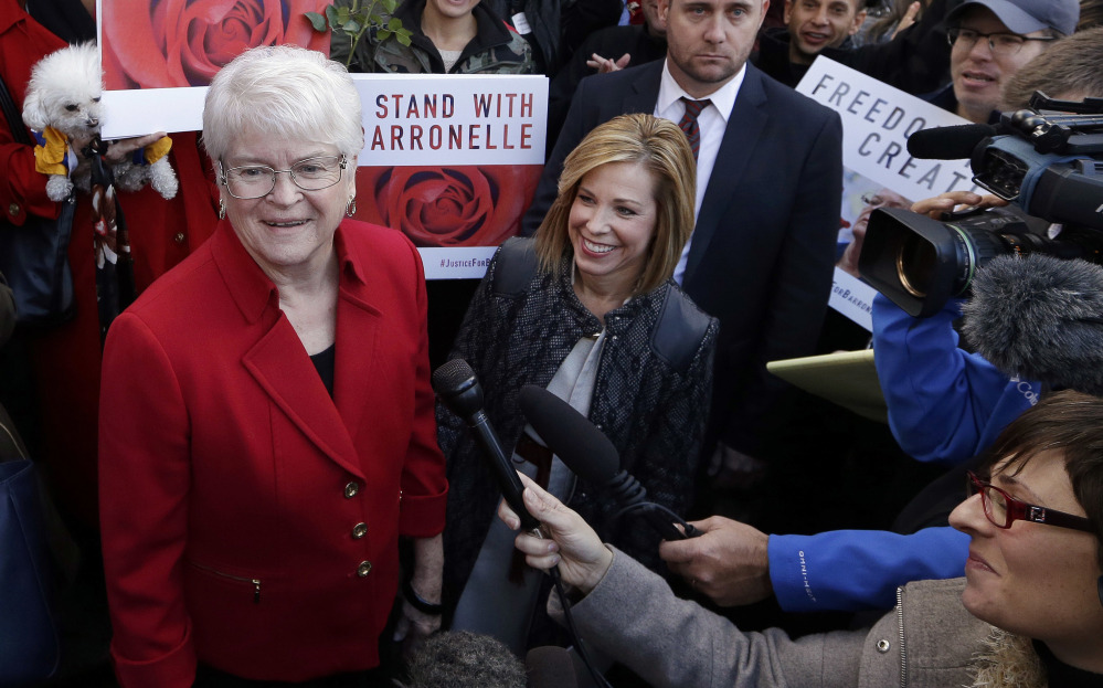 Barronelle Stutzman, left, a Richland, Wash., florist who was fined for denying service to a gay couple in 2013, smiles as she is surrounded by supporters after a hearing Nov. 16, 2016, before Washington's Supreme Court in Bellevue, Wash. Curt Freed, left, and Robert Ingersoll sued florist Barronelle Stutzman for refusing to provide services for their wedding.
