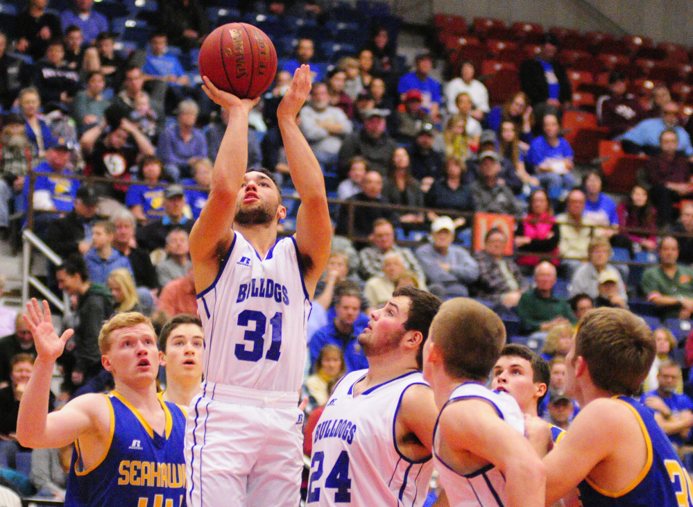 Madison guard Nicholas Morales gets off a shot during a Class C South quarterfinal Monday at the Augusta Civic Center. The Bulldogs beat Boothbay, 63-41.