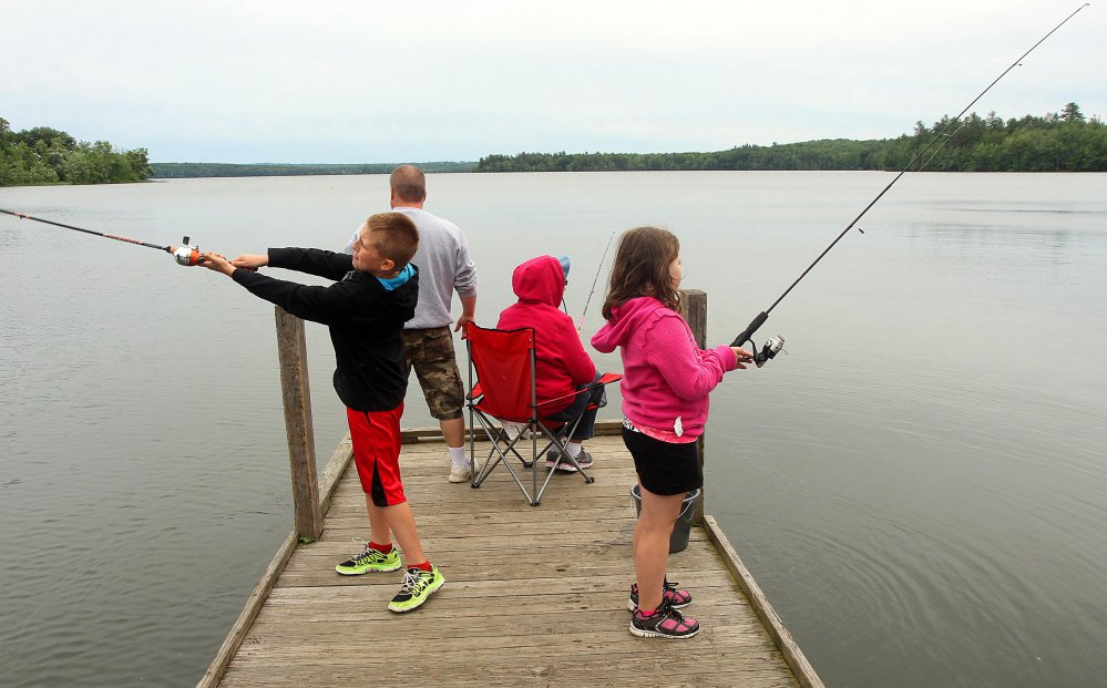 A Waterville family fishes in 2014 on China Lake in East Vassalboro. The Kennebec Water District, which owns the west basin shorefront there and draws its water supply from the lake for 30,000 customers, opposes legislation that would charge district users a $5 fee in order to help improve the lake's water quality.