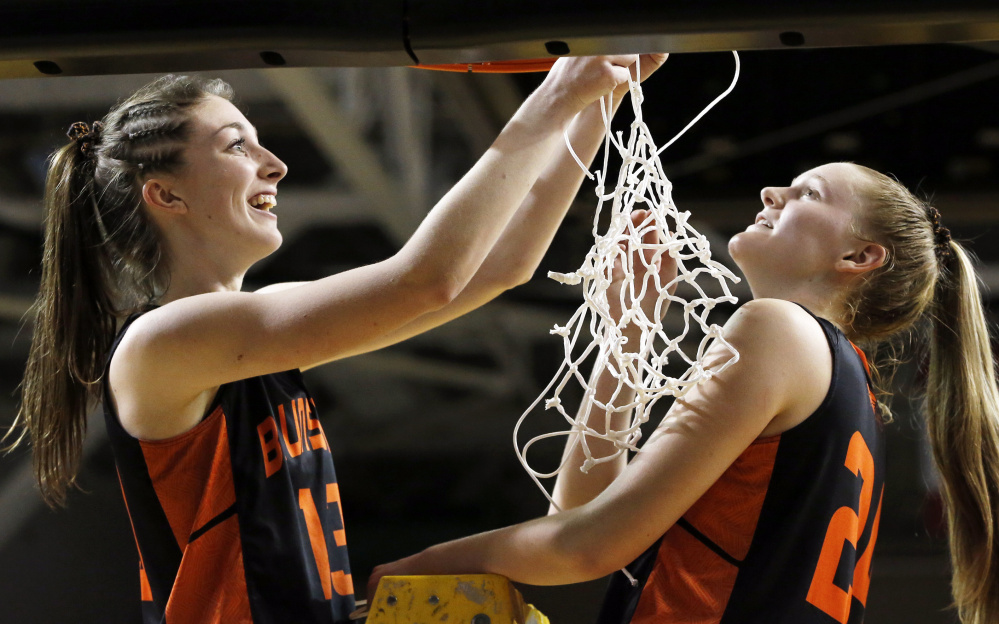 Aidan Sachs, left, and Brooke Barter share the honor of cutting the final strands of the net after Brunswick beat Greely to win the Class A South final.