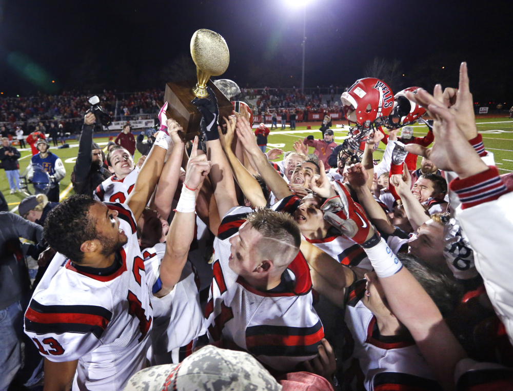 PORTLAND, ME - NOVEMBER 18: Class C football state championship game. Wells celebrates with their gold ball after shutting out MDI in the championship game. (Photo by Derek Davis/Staff Photographer)